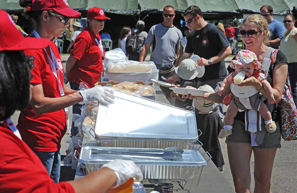 . Lisa Bielanski, right,  and her 4 month old daughter Lola, get lunch served to them from volunteer members of the Emergency Disaster Services of the Salvation Army at Buckley Air Force base in Aurora, CO on August 4, 2013.  The event was part of the 140th Wing Family Day for members of the Colorado National Guard.  Much of the money raised during the day goes to the Colorado National Guard Family Support System that helps take care of families when their loved ones have been deployed.  The Salvation Army was on hand to show their continued support for the armed services.  Photo by Helen H. Richardson/The Denver Post)