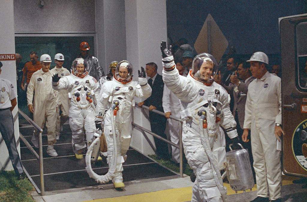 """. FILE - In this July 16, 1969 file photo, Neil Armstrong waving in front, heads for the van that will take the crew to the rocket for launch to the moon at Kennedy Space Center in Merritt Island, Fla. Armstrong and fellow astronaut Edwin \""""Buzz\"""" Aldrin spent nearly three hours walking on the moon, collecting samples, conducting experiments and taking photographs. In all, 12 Americans walked on the moon from 1969 to 1972.  (AP Photo/File)"""