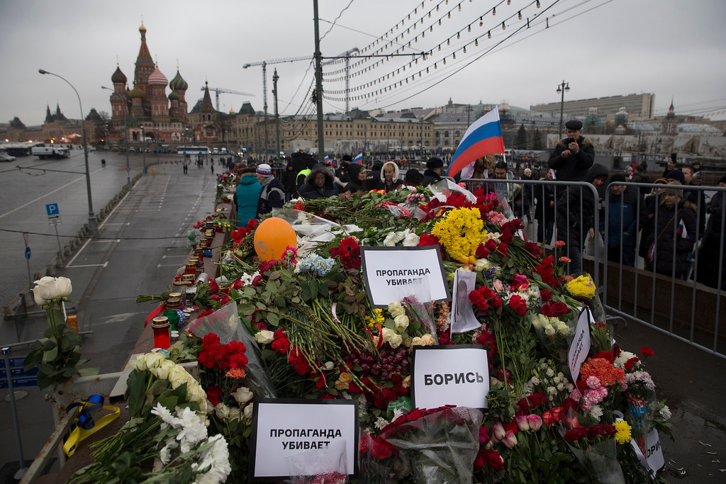 . Flowers and pesters reading \' propaganda kills!\' are seen at the place where Boris Nemtsov, a charismatic Russian opposition leader and sharp critic of President Vladimir Putin, was gunned down on Friday, Feb. 27, 2015 near the Kremlin, with the Kremlin Wall is in the background in Moscow, Russia, Sunday, March 1, 2015. Russian investigators, politicians and political commentators on state television on Saturday covered much ground in looking for the reason Nemtsov was gunned down in the heart of Moscow, but they sidestepped one possibility, that he was murdered for his relentless opposition to Putin. (AP Photo/Pavel Golovkin)