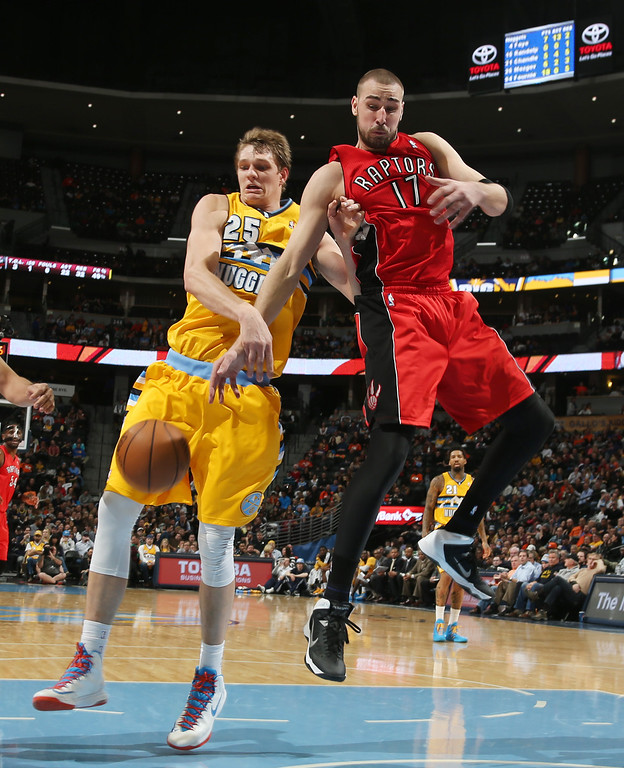 . Denver Nuggets center Timofey Mozgov, left, of Russia, fights for control of loose ball with Toronto Raptors center Jonas Valanciunas, of Lithuania, in the fourth quarter of an NBA basketball game in Denver on Friday, Jan. 31, 2014. (AP Photo/David Zalubowski)