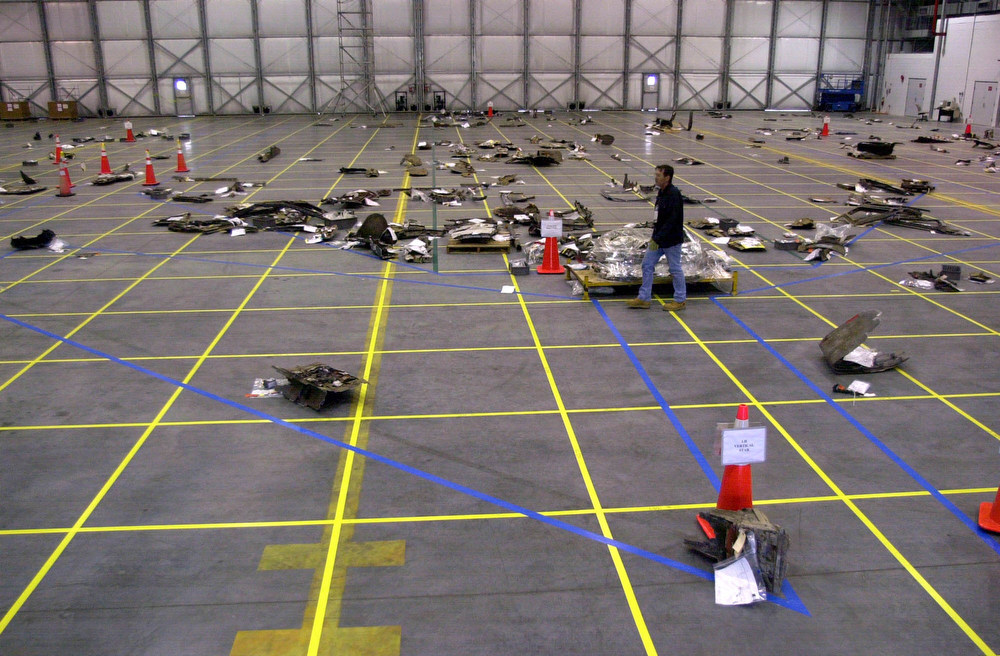 . A member of the space shuttle Columbia reconstruction project team walks through the wreckage that is laid out on the floor of this hangar at the Kennedy Space Center in Cape Canaveral, Fla., Friday Feb. 21, 2003.  The debris is being layed out on a grid to aid in the investigation of the Columbia accident.  (AP Photo/Peter Cosgrove)
