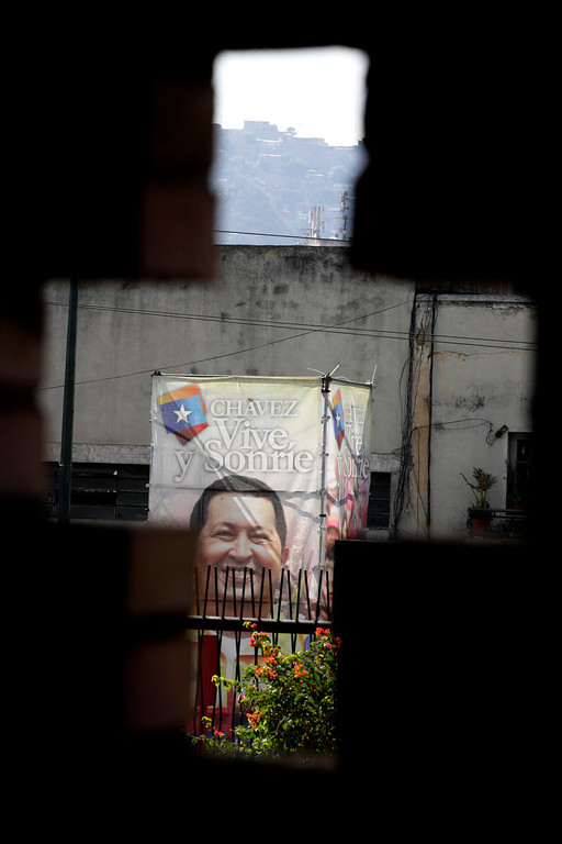 """. A poster of Venezuela\'s President Hugo Chavez is seen through a cross-shaped window, from inside the military hospital\'s chapel, in Caracas, Venezuela, Tuesday, March 5, 2013. A brief statement read on national television by Communications Minister Ernesto Villegas late Monday carried the sobering news about the charismatic 58-year-old leader\'s deteriorating health. Villegas said Chavez is suffering from \""""a new, severe infection.\"""" The state news agency identified it as respiratory. (AP Photo/Ariana Cubillos)"""