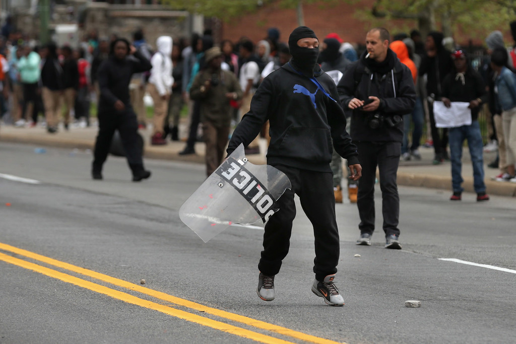 . BALTIMORE, MD - APRIL 27:  Young person holds a Baltimore Police shield outside the Mondawmin Mall during protests following the funeral of Freddie Gray April 27, 2015 in Baltimore, Maryland. Gray, 25, who was arrested for possessing a switch blade knife April 12 outside the Gilmor Homes housing project on Baltimore\'s west side. According to his attorney, Gray died a week later in the hospital from a severe spinal cord injury he received while in police custody.  (Photo by Chip Somodevilla/Getty Images)