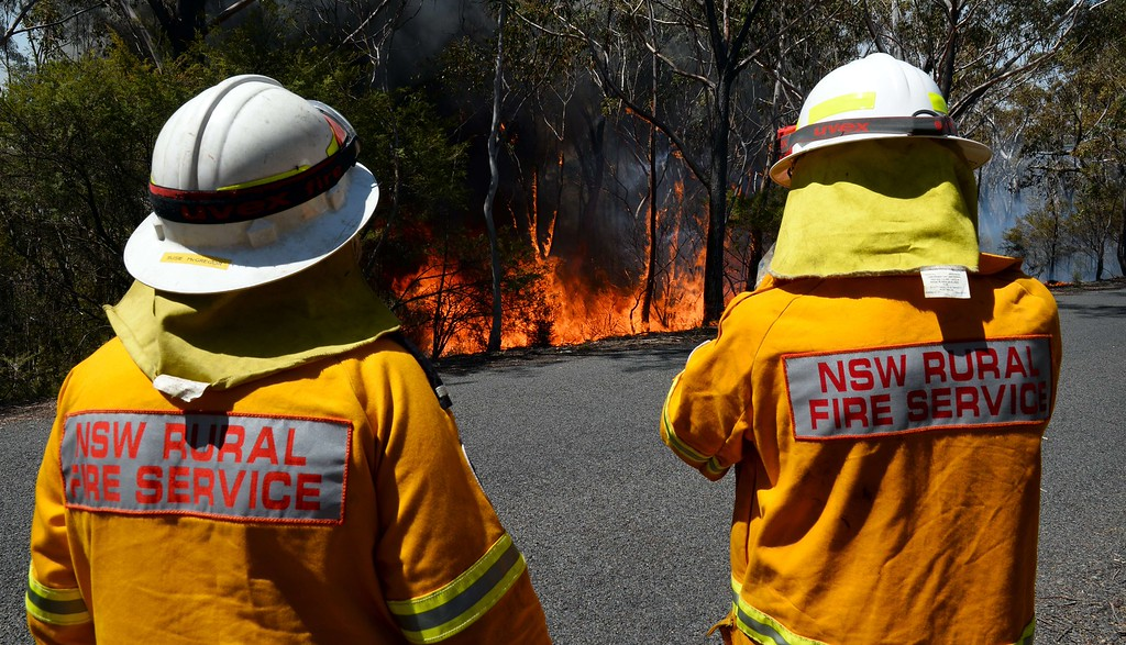 """. Firefighters monitor a back burn near Mount Victoria in the Blue Mountains on October 21, 2013, as volunteer fire brigades race to tame an enormous blaze, with officials warning it could merge with others to create a \""""mega-fire\"""" if weather conditions worsen.    AFP PHOTO/William WEST/AFP/Getty Images"""