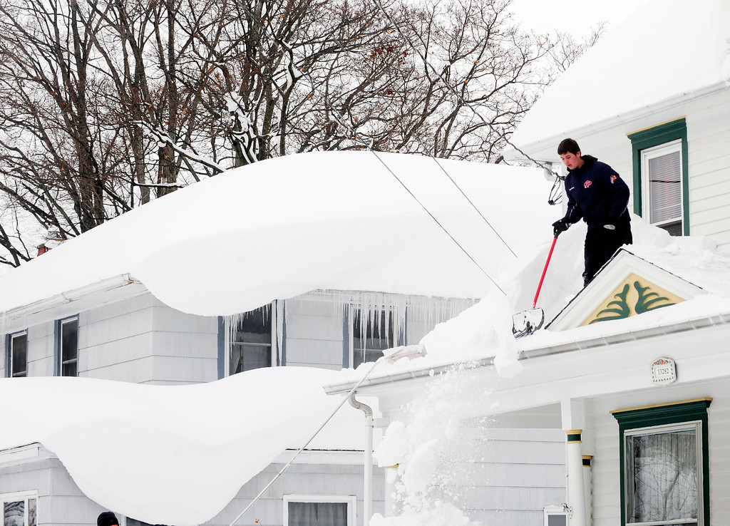 . Andrew Zelak cleans the snow from his roof on Irving Place in Alden, N.Y. Thursday, Nov. 20, 2014. A new blast of lake-effect snow roared through western New York with thunder and lightning on Thursday, raising to nearly 6 feet the three-day total in parts of the Buffalo area. The weight of the snow has caused problems around the area with roofs collapsing and structures fracturing. (AP Photo/Gary Wiepert)