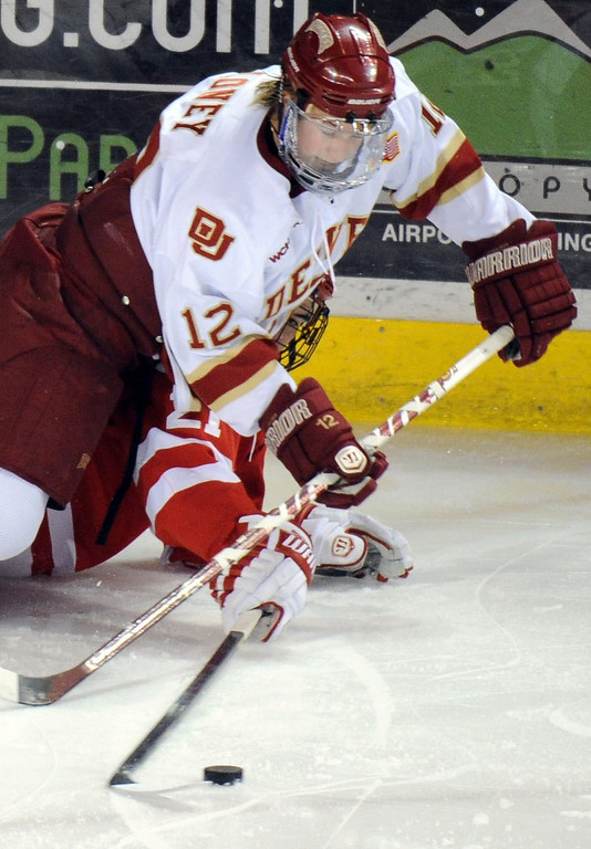 . University of Denver Ty Loney(12), top, controls the puck against  Boston University Sean Escobedo (21), bottom, in the 1st period of the game at Magness Arena on in Denver on Saturday, Dec. 29, 2012. Hyoung Chang, The Denver Post