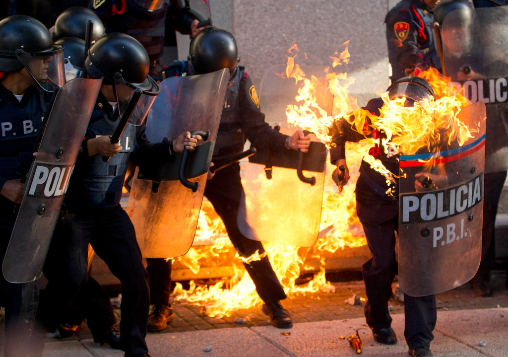 . In this Wednesday, Oct. 2, 2013 photo, a police officer is engulfed in flames after being hit by a Molotov cocktail thrown by protesters marking the anniversary of the Tlatelolco massacre in Mexico City. Thousands of teachers and students blocked Mexico City\'s main thoroughfares during rush hour to honor victims of the massacre while pledging to fight to undo an overhaul of the education system. A small group of self-described anarchists clashed with riot police, who used tear gas after the activists threw firebombs, bottles and rocks. (AP Photo/Eduardo Verdugo)