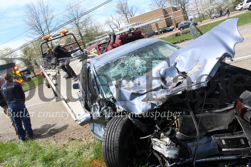 Harold Aughton/Butler Eagle: A tow truck driver removes the remants of a blue sedan from an accident along Route 68 by the Conquonessing elementary school Wednesday afternoon, April 24.