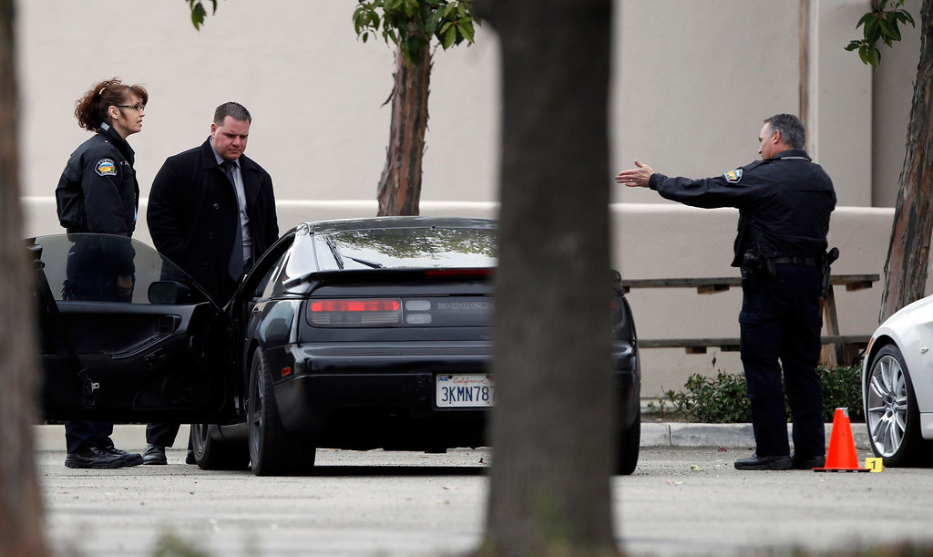 . Police authorities process a black car, next to a stolen white car (R), in the parking lot of a Tustin computer store after a gunman went on a shooting spree in suburban southern California February 19, 2013REUTERS/Alex Gallardo