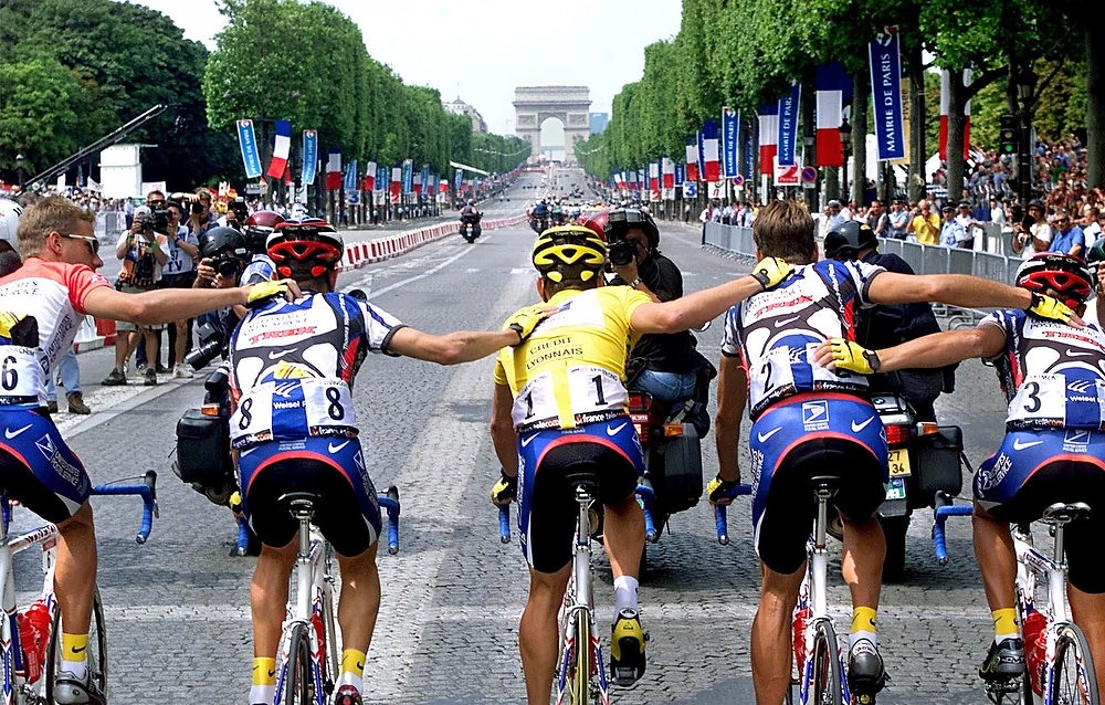 Description of . Tour de France overall leader Lance Armstrong of Austin, Texas, center, and his teammates from left: Benoit Joachim of Luxembourg, Kevin Livingstone and George Hincapie of the United States, and Vjatceslav Ekimov of Russia, ride up the Champs Elysees avenue during the 21st and final stage of the Tour de France cycling race in Paris on Sunday, July 23, 2000. (AP Photo/Laurent Rebours)