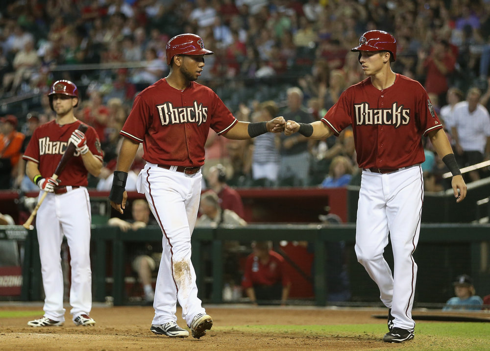 . Alfredo Marte #17 (C) of the Arizona Diamondbacks high fives Jake Lamb #19 after Lamb scored a fourth inning run against the Colorado Rockies during the MLB game at Chase Field on August 10, 2014 in Phoenix, Arizona.  (Photo by Christian Petersen/Getty Images)