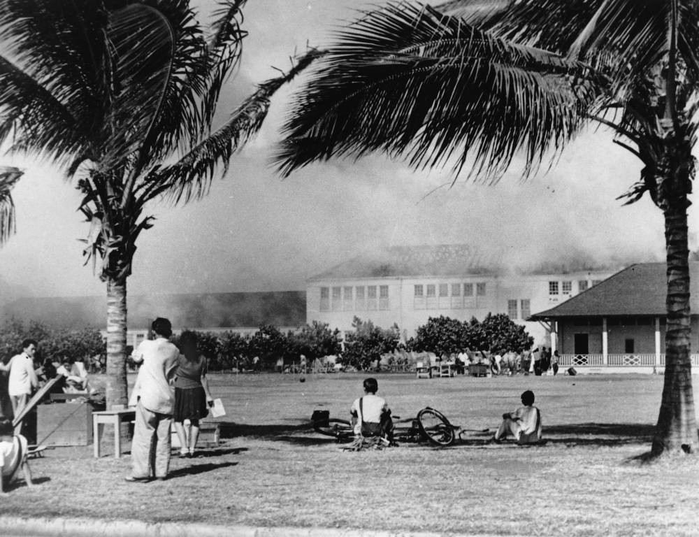 . In this Dec. 7, 1941, file photo, students of the Lunalilo High School in the Waikiki district of Honolulu watch their school burn after the roof of the main building, at center, was hit by a bomb during the Japanese attack on Pearl Harbor, Hawaii.  (AP Photo/File)