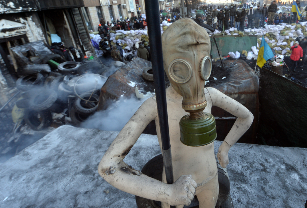 . A mannequin wearing a gas mask and taken among debris burnt from children clothes shop stands near a barricade in the center of Kiev on January 24, 2014. Ukrainian protesters Friday expanded their protest camp in Kiev closer to the administration of President Viktor Yanukovych, after crisis talks to end Ukraine\'s worst crisis since its 1991 independence ended in deadlock. After five days of clashes that activists say left five dead, Ukraine\'s three main opposition leaders held several hours of talks with Yanukovych late Thursday but the minor concessions they announced were greeted with derision by protesters. (SERGEI SUPINSKY/AFP/Getty Images)