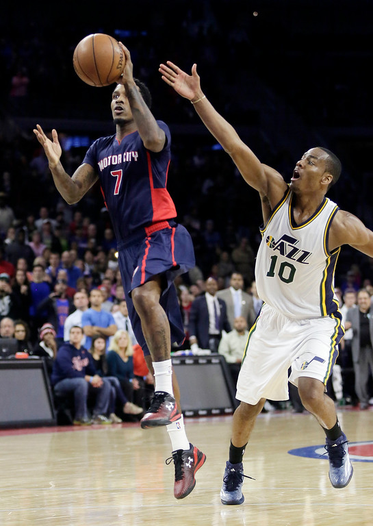. Detroit Pistons\' Brandon Jennings (7) takes a shot as Utah Jazz\'s Alec Burks (10) defends during the second half of an NBA basketball game Sunday, Nov. 9, 2014, in Auburn Hills, Mich. The Jazz defeated the Pistons 97-96. (AP Photo/Duane Burleson)