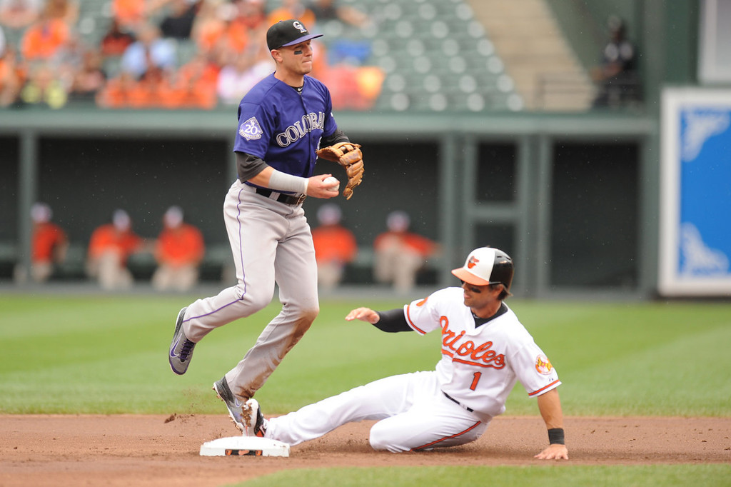 . Troy Tulowitzki #2 of the Colorado Rockies forces out Brian Roberts #1 of the Baltimore Orioles at second base in the second inning during a baseball game on August 18, 2013 at Oriole Park at Camden Yards in Baltimore, Maryland.  (Photo by Mitchell Layton/Getty Images)