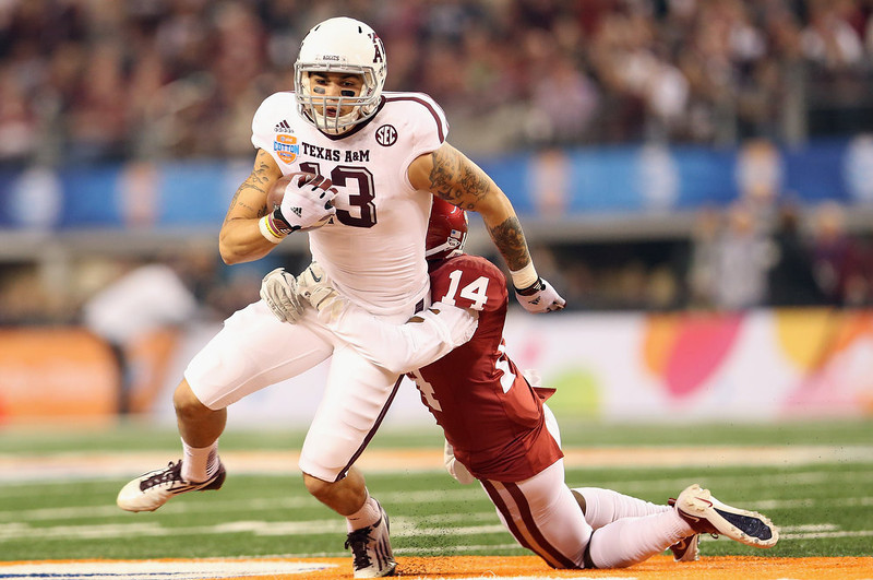. Mike Evans #13 of the Texas A&M Aggies runs the ball against Aaron Colvin #14 of the Oklahoma Sooners during the Cotton Bowl at Cowboys Stadium on January 4, 2013 in Arlington, Texas.  (Photo by Ronald Martinez/Getty Images)