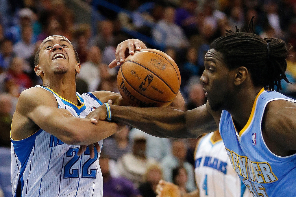 . New Orleans Hornets guard Brian Roberts (22) gets fouled by Denver Nuggets forward Kenneth Faried (35) in the first half of an NBA basketball game in New Orleans, Monday, March 25, 2013. (AP Photo/Bill Haber)
