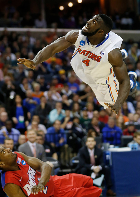. Florida center Patric Young (4) watches his shot as Dayton forward Dyshawn Pierre (21) falls to the floor during the second half in a regional final game at the NCAA college basketball tournament, Saturday, March 29, 2014, in Memphis, Tenn. (AP Photo/John Bazemore)