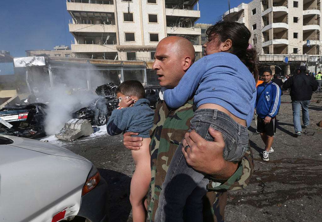 . A Lebanese army soldier carries two injured children away from the site of an explosion near the Kuwaiti Embassy and Iran\'s cultural center, in the suburb of Beir Hassan, Beirut, Lebanon, Wednesday, Feb. 19, 2014.  (AP Photo/Hussein Malla)