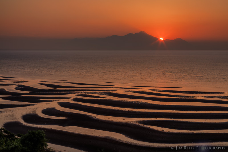 Low tide reveals beautiful patterns of sand bars at sunset. Okoshiki Beach in southern Japan.