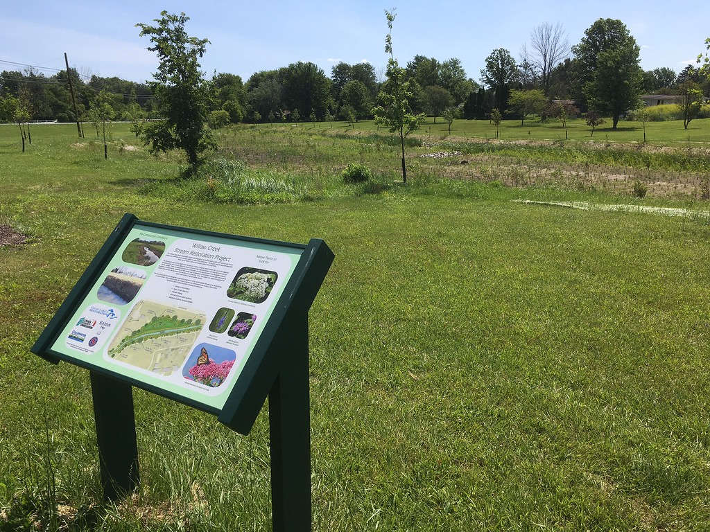 . Richard Payerchin - The Morning Journal <br> An informational sign explains the habitat restoration at flood control measures completed this year at the Willow Creek restoration site in the Eaton Township Community Park on June 28, 2017.