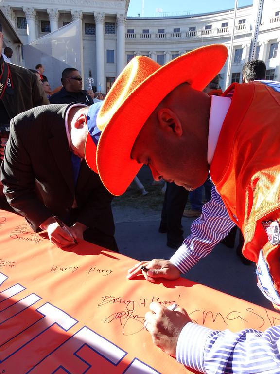 . Mayor Hancock signs the Broncos\' banner at the Pep Rally on 1/17/14!