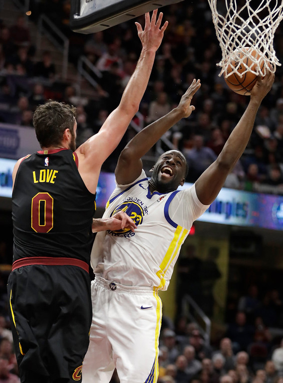 . Golden State Warriors\' Draymond Green (23) drives to the basket against Cleveland Cavaliers\' Kevin Love (0) in the second half of an NBA basketball game, Monday, Jan. 15, 2018, in Cleveland. (AP Photo/Tony Dejak)