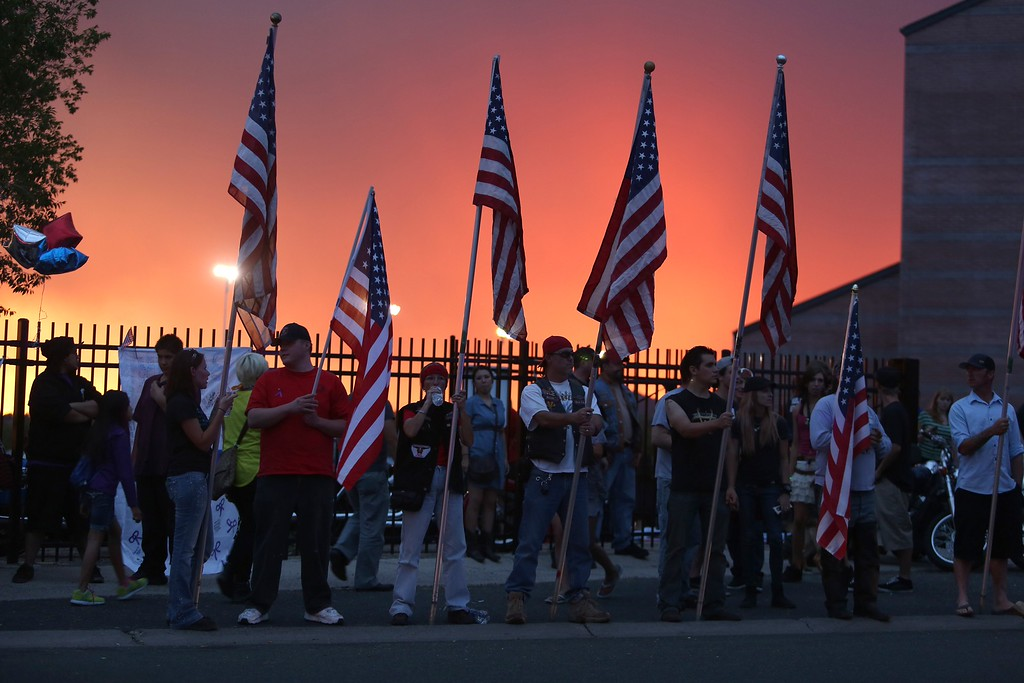 . People hold national US flags outside a vigil and memorial gathering at the Prescott High School in Prescott, Arizona on July 2, 2013.   AFP PHOTO / KRISTA  Kennell/AFP/Getty Images