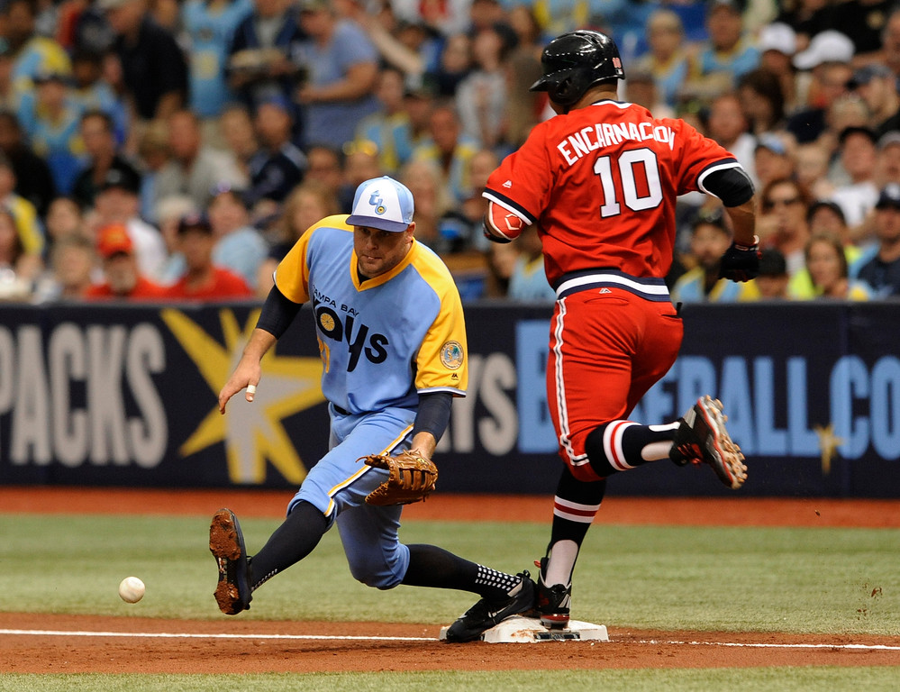 . Cleveland Indians\' Edwin Encarnacio (10) beats the throw to Tampa Bay Rays first baseman Lucas Duda, left, from third baseman Trevor Plouffe for an infield hit during the first inning of a baseball game Saturday, Aug. 12, 2017, in St. Petersburg, Fla. Both teams are wearing throwback jerseys. (AP Photo/Steve Nesius)