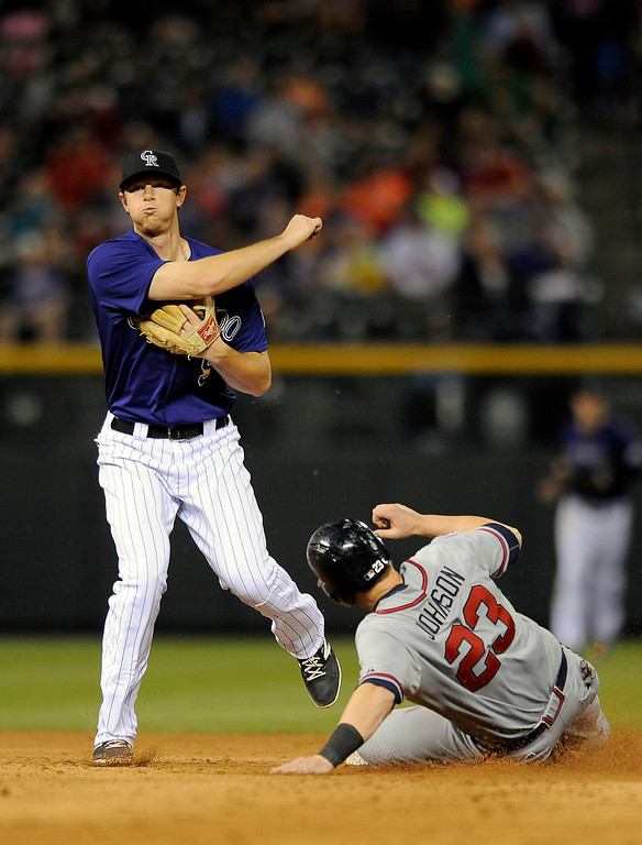 . Colorado Rockies second baseman DJ LeMahieu, left, forces out Atlanta Braves Chris Johnson at second base and makes the throw to first base to putout Braves Andrelton Simmons and turn the double play in the eighth inning of a baseball game on Monday, June 9, 2014, in Denver. (AP Photo/Chris Schneider)