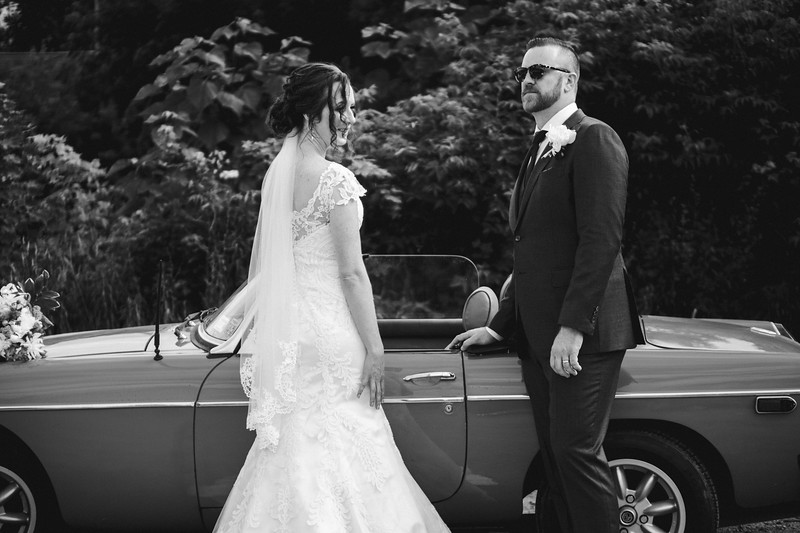 The groom is about to open the drivers side door of the convertible for the bride.