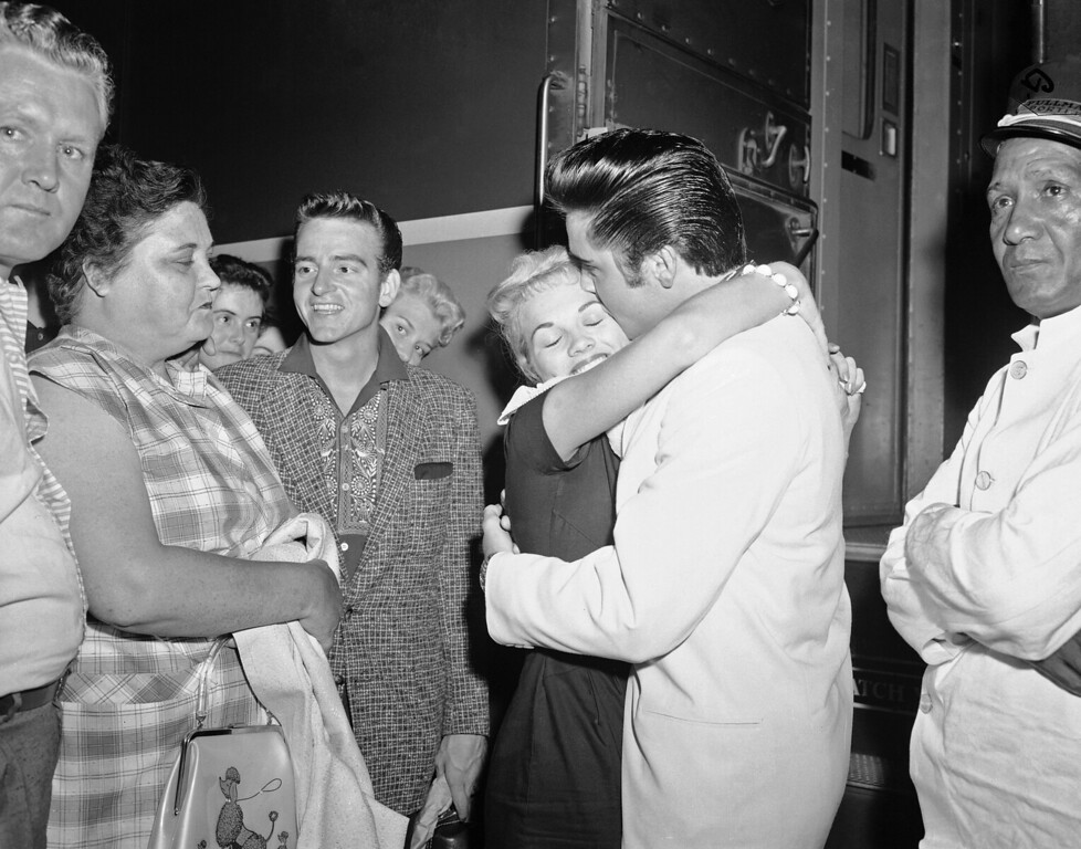 . Elvis Presley embraces Anita Wood, 19-year-old Memphis television personality, as he prepared to board a train at Central Station in Memphis, Tennessee on August 29, 1957. Presley is leaving on a tour of the northwest. Mr. and Mrs. Presley look on.  (AP Photo/FJG)