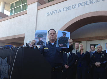 . Santa Cruz Police Chief Kevin Vogel holds up the photographs of his officers detective Sgt. Loran \'Butch\' Baker and detective Elizabeth Butler during an emotional press conference Wednesday. (J.M. Brown/Sentinel)