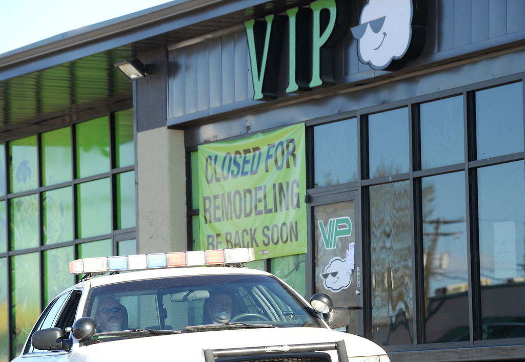 . Denver Police officers stay out in front of VIP Cannabis, located at 2949 W. Alameda Ave., after the Drug Enforcement Agency officials raided it in the morning, April 30, 2014. The marijuana dispensary was previously raided in November 2013. (Photo by RJ Sangosti/The Denver Post)