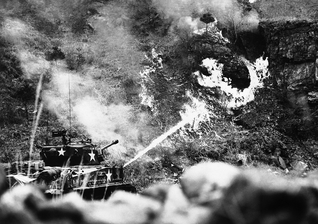 . A 25th Division tank uses a flame thrower on an enemy pillbox deeply emplaced in a hillside near Korea?s Han River front on March 30, 1951. The scene is reminiscent of Pacific island warfare during World War II. (AP Photo)