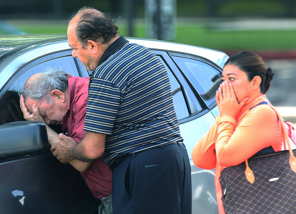 . A man is comforted after finding out that a relative drowned in her truck at 5757 Ranchester in Houston on Tuesday, May 26, 2015. A holiday weekend of storms dumped record rainfall on the American heartland, caused major flooding and spawned tornadoes. More than 1,000 homes have been damaged or destroyed in Texas, and thousands of residents are displaced. (Thomas B. Shea/Houston Chronicle via AP)