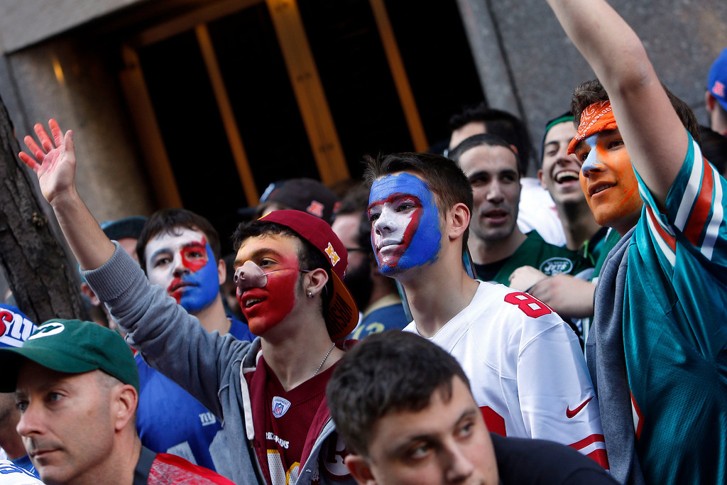 . Football fans wave to passersby as they wait outside Radio City Music Hall before the first round of the NFL football draft on Thursday, April 25, 2013, in New York. (AP Photo/Jason DeCrow)