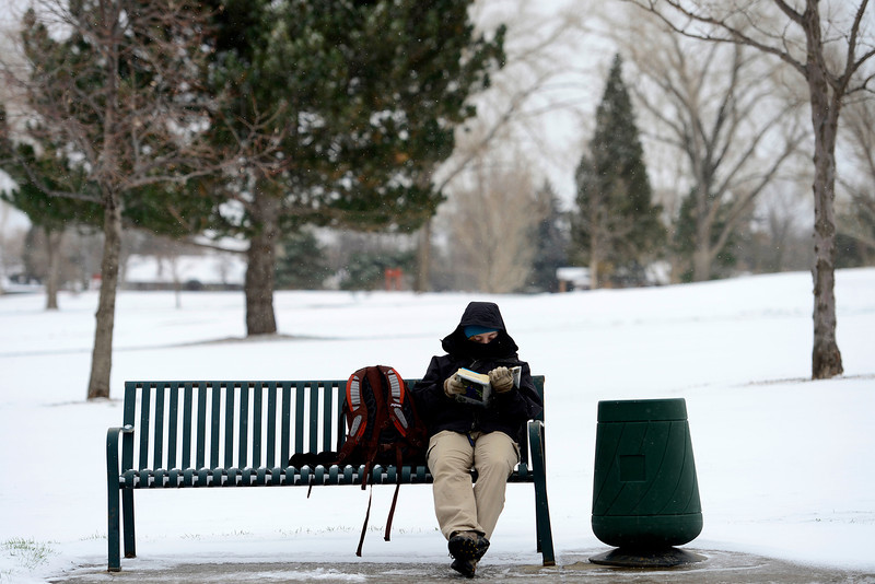 . Jennifer Nixon, a Denver Zoo employee, sits on a bench as she waits for a bus on 28th. Temperatures in Denver reached the mid-teens. (Photo by AAron Ontiveroz/The Denver Post)
