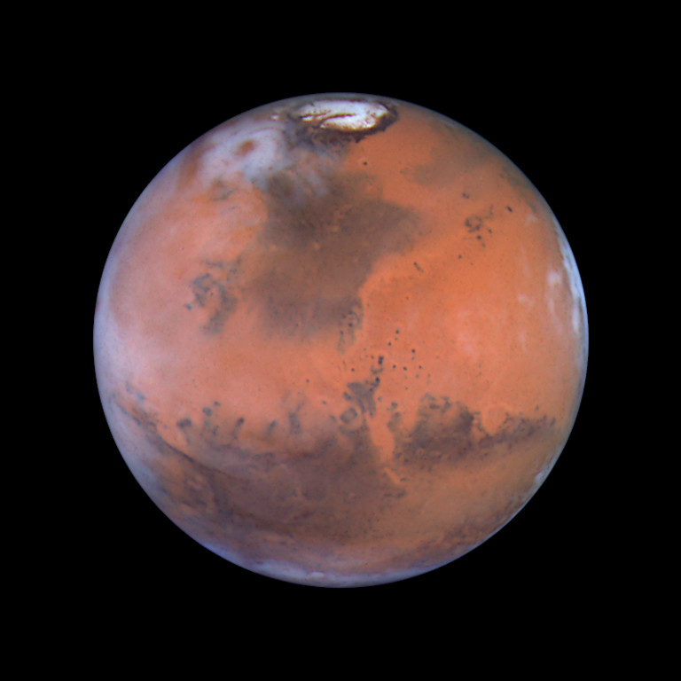 . 1999: Mars 2000  This image is centered near the location of the Pathfinder landing site. Dark sand dunes that surround the polar cap merge into a large, dark region called Acidalia. This area, as shown by images from the Hubble telescope and other spacecraft, is composed of dark, sand-sized grains of pulverized volcanic rock. Below and to the left of Acidalia are the massive Martian canyon systems of Valles Marineris, some of which form long linear markings that were once thought by some to be canals. Early morning clouds can be seen along the left limb of the planet, and a large cyclonic storm composed of water ice is churning near the polar cap. Credit: Steve Lee (University of Colorado), Jim Bell (Cornell University), Mike Wolff (Space Science Institute), and NASA