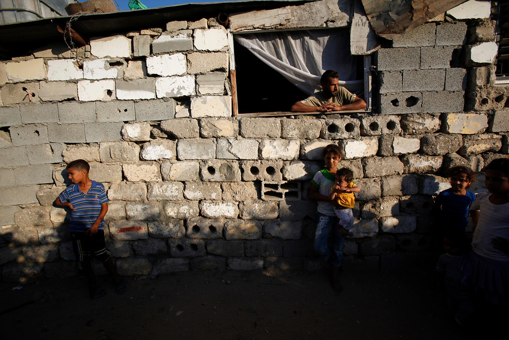 . In this Tuesday, Oct. 1, 2013 photo, Majed Alwadiya, 31, watches children of his extended family members as they play outside their family house in Gaza City. Thirty-eight people live a makeshift house made from scrap wood, salvaged concrete bricks and corrugated aluminum. (AP Photo/Adel Hana)