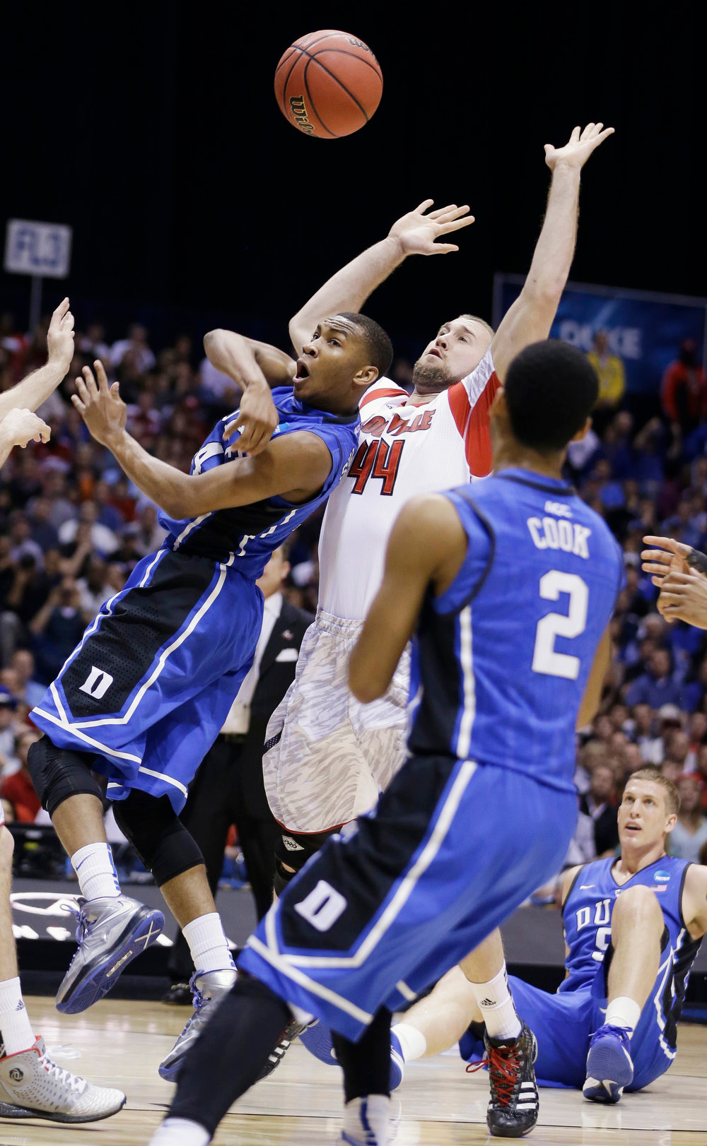 Description of . Duke guard Rasheed Sulaimon passes the ball to Quinn Cook (2) under pressure from Louisville forward Stephan Van Treese (44) during the first half of the Midwest Regional final in the NCAA college basketball tournament, Sunday, March 31, 2013, in Indianapolis. (AP Photo/Darron Cummings)