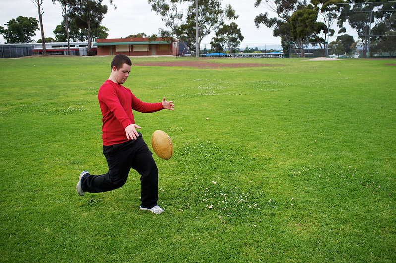Sixteen-year-old boy kicking football at a suburban park