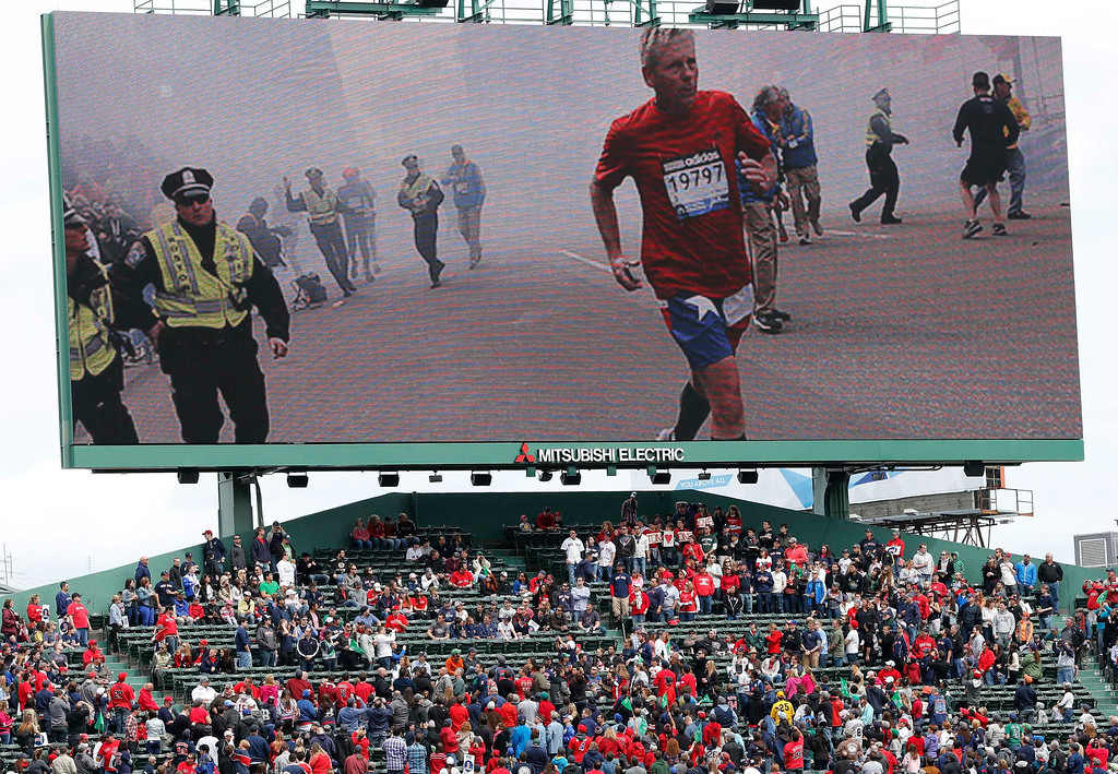 . Scenes from the Boston Marathon bombings is displayed on an outfield screen before a baseball game between the Boston Red Sox and the Kansas City Royals in Boston, Saturday, April 20, 2013. (AP Photo/Michael Dwyer)