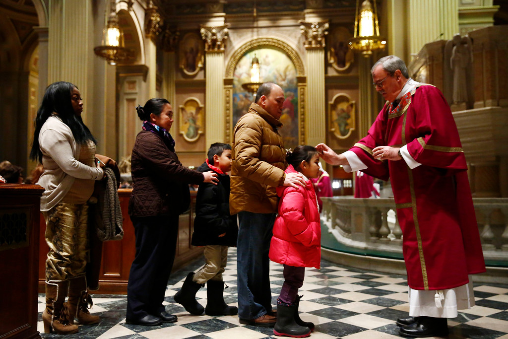 . Deacon Sam Bianco places ash on a worshiper\'s forehead during an Ash Wednesday Mass at the Cathedral Basilica of Saints Peter and Paul in Philadelphia on Wednesday, Feb. 18, 2015. Ash Wednesday marks the beginning of Lent, a time when Christians prepare for Easter through acts of penitence and prayer. (AP Photo/Matt Rourke)