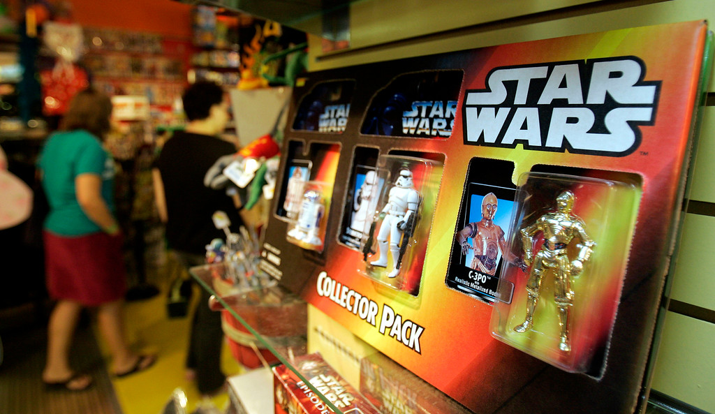 ". Two customers walk past a Hasbro ""Star Wars\"" collector pack, Monday, July 24, 2006, at Big Fun toy store in Cleveland Heights, Ohio. Hasbro Inc., the nation\'s second-largest toy maker, said Monday that earnings and revenue declined in the second quarter, due in part to an anticipated drop in \""Star Wars\"" product sales. The profit was in line with expectations while the lower revenue figures still topped what analysts estimated, and the company said it remains on track to deliver financial goals for the full year. (AP Photo/Tony Dejak)"