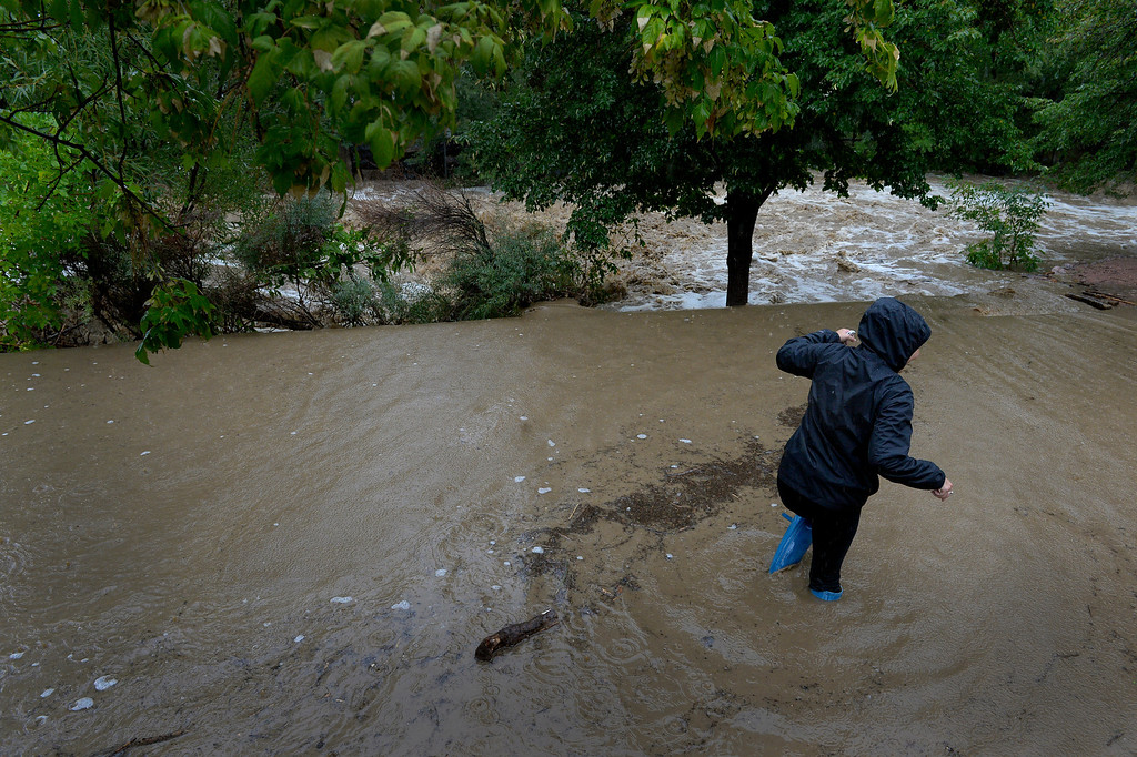 . BOULDER, CO. - SEPTEMBER12:  A woman walk along a flooded bike path along Boulder Creek in Boulder CO September 12, 2013. Record-breaking rain turned normally quiet creeks into raging, brown torrents that swept through Boulder on Thursday, flooding homes, swamping cars and closing roads and schools. (Photo By Craig F. Walker / The Denver Post)