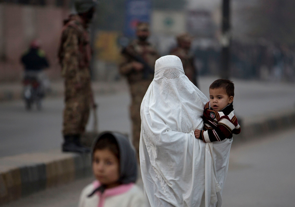 . A Pakistani woman walks past a school attacked by the Taliban in Peshawar, Pakistan, Tuesday,  Tuesday, Dec. 16, 2014. Taliban gunmen stormed a military-run school in the northwestern Pakistani city of Peshawar on Tuesday, killing and wounding scores, officials said, in the highest-profile militant attack to hit the troubled region in months. (AP Photo/B.K. Bangash)
