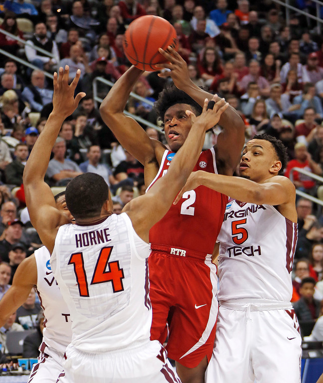 . Alabama \'s Collin Sexton (2) gets off a pass between Virginia Tech\'s P.J. Horne (14) and Justin Robinson (5) during the first half of an NCAA men\'s college basketball tournament first-round game, in Pittsburgh, Thursday, March 15, 2018. (AP Photo/Gene J. Puskar)