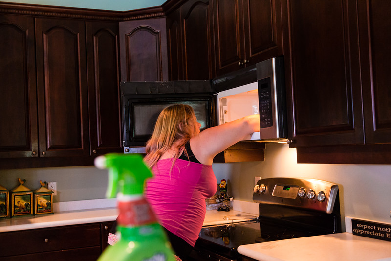 """Tabitha Franks, 31, of Loxahatchee, Florida, cleans the microwave in the kitchen at the All About Recovery younger women's sober home in Loxahatchee, Florida on Friday, June 24, 2016. Residents are required to keep the sober home clean, but once a week, the residents  are assigned an area of the sober house to """"deep clean"""". (Joseph Forzano / The Palm Beach Post)"""