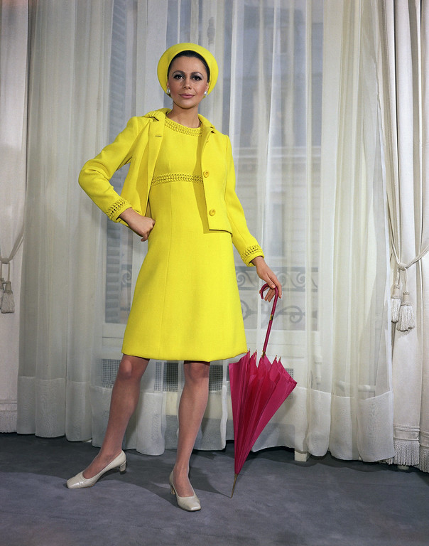 . Zeste, a yellow woolen dress trimmed with braid. Worn with matching jacket, and shocking pink umbrella by Pierre Balmain, yellow woolen beret in 1967. (AP Photo)